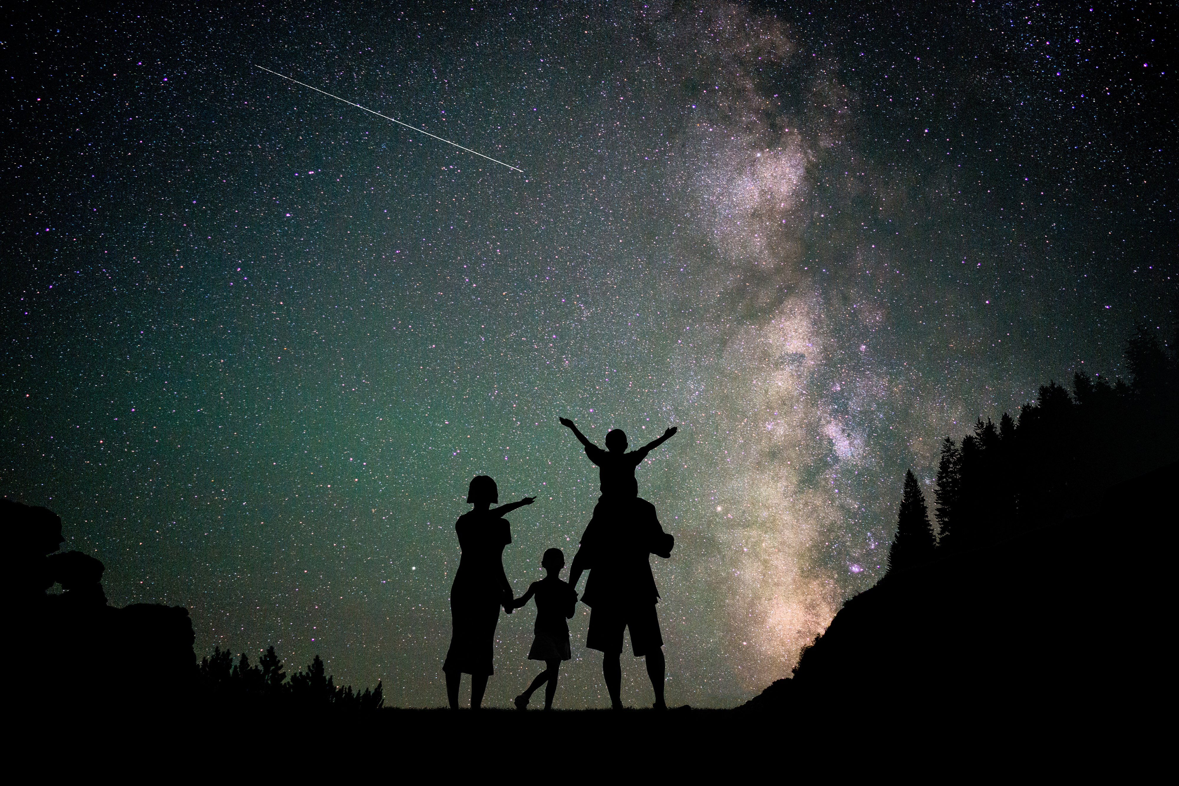 Happy family silhouette with Milky Way and beautiful night sky full of