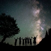 Happy kids group silhouette with Milky Way and beautiful night sky ful